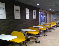 Indoor image of McDonalds with yellow benches and white tables.