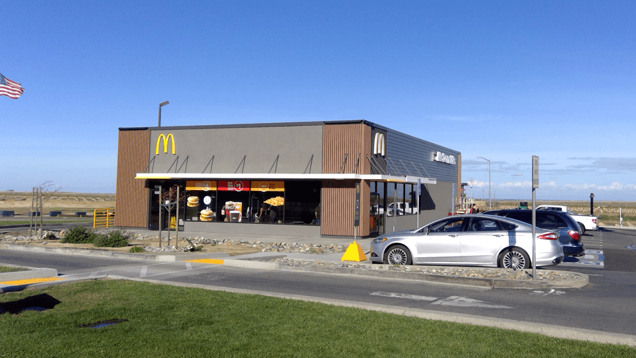 Outdoor image of McDonalds showing the main entrance and parking lot.